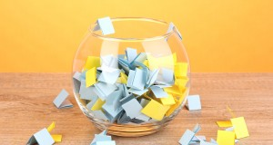 Pieces of paper for lottery in vase on wooden table on yellow background